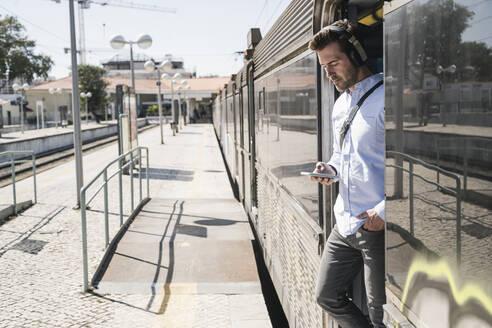 Young man with headphones and smartphone standing in train door - UUF19756