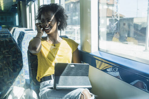 Happy young woman with earphones and tablet on a train - UUF19765