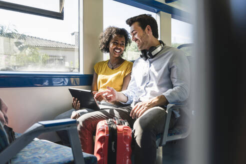 Happy young couple using tablet in a train - UUF19792