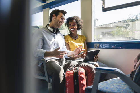 Happy young couple using tablet in a train - UUF19795