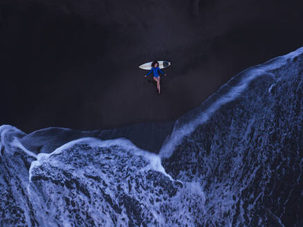 Aerial view of young woman with surfboard at the beach, Kedungu beach, Bali, Indonesia - KNTF03777