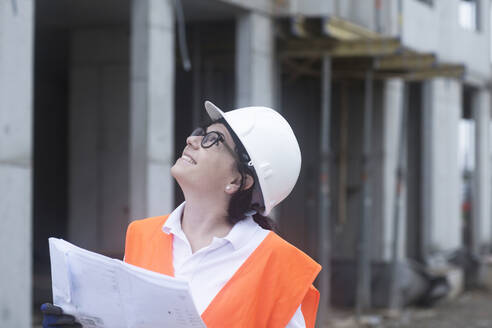 Female construction engineer looking up, holding construction plan - SGF02557