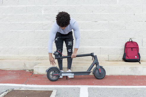Young man folding e-scooter - JPTF00371