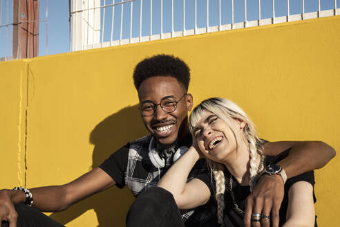 Portrait of laughing young couple against yellow wall - RCPF00157