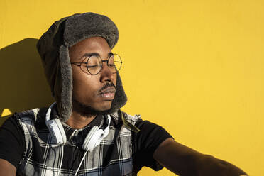 Portrait of young man wearing with headphones wearing cap and metal-rimmed glasses against yellow wall - RCPF00181