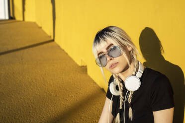 Portrait of young woman with headphones and coloured sunglasses in front of yellow wall - RCPF00187