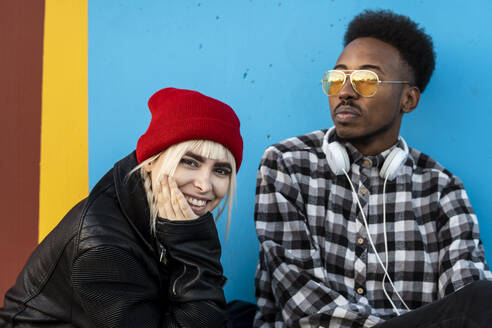 Portrait of young couple against blue wall - RCPF00199