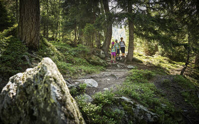 Mother with two children hiking in forest, Passeier Valley, South Tyrol, Italy - DIKF00320
