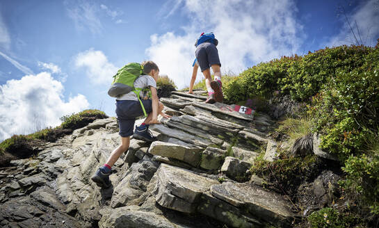 Boy and girl climbing up rock in the mountains, Passeier Valley, South Tyrol, Italy - DIKF00335