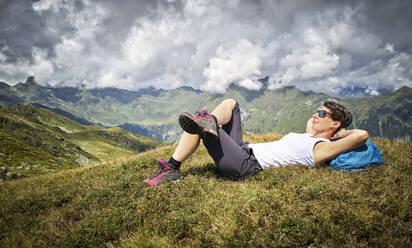 Woman having a break from hiking lying on alpine meadow, Passeier Valley, South Tyrol, Italy - DIKF00338