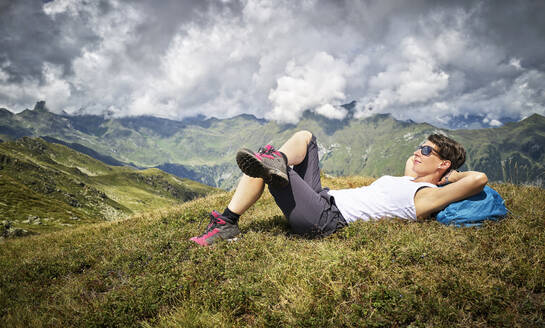 Woman having a break from hiking lying on alpine meadow, Passeier Valley, South Tyrol, Italy - DIKF00338