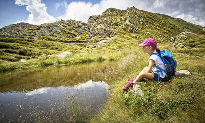 Girl having a break from hiking sitting at a mountain lake, Passeier Valley, South Tyrol, Italy - DIKF00341