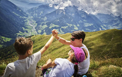 Happy mother with two children having a break from hiking in alpine scenery, Passeier Valley, South Tyrol, Italy - DIKF00344