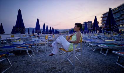Mature woman realxing on the beach at dusk, San Bartolomeo al Mare, Italy - DIKF00352