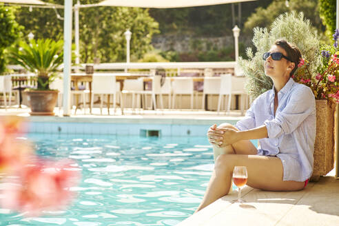 Mature woman sitting at poolside with glass of blush wine - DIKF00364