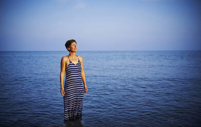 Mature woman with eyes closed standing in the sea enjoying sunset, Italy - DIKF00367