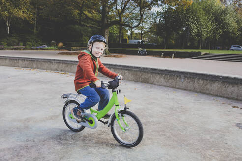 Portrait of smiling little boy riding bicycle - IHF00223