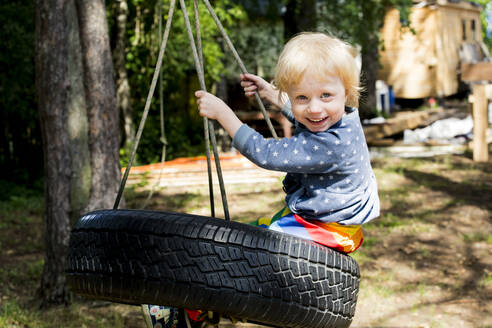 Portrait of happy toddler girl sitting on tire swing - IHF00226