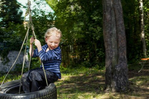 Happy little boy sitting on tire swing - IHF00229