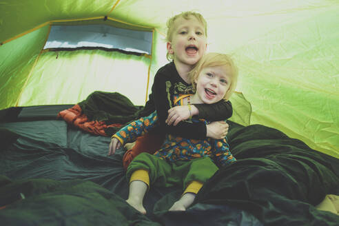 Portrait of siblings playing together in a tent - IHF00238
