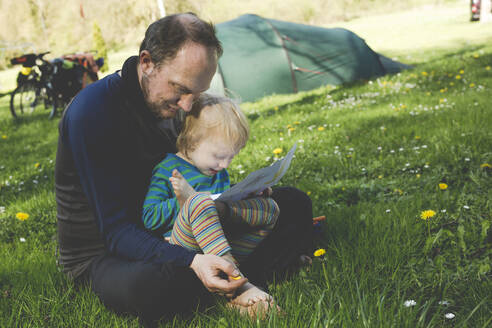 Father and his little daughter sitting together on a meadow with map - IHF00247