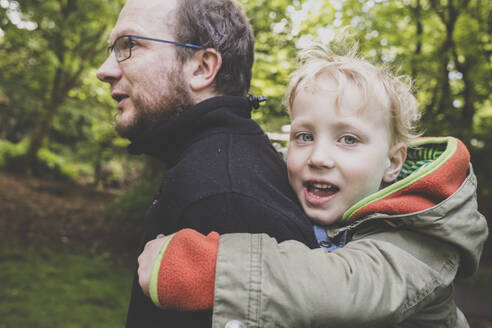 Father giving his little son a piggyback ride - IHF00253