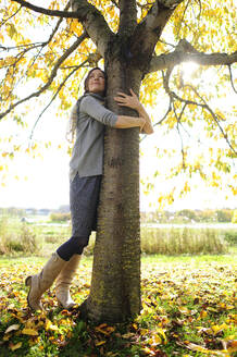 Portrait of women tree hugging - ECPF00797