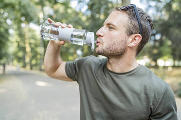 Man drinking water after workout outdoors - FBAF01097