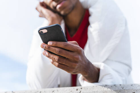 Close-up of young man using smartphone outdoors - AFVF04649