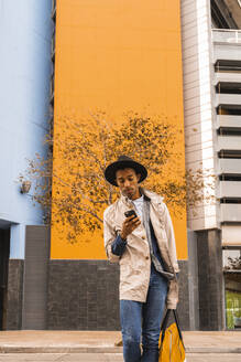 Fashionable young man using smartphone outdoors - AFVF04670