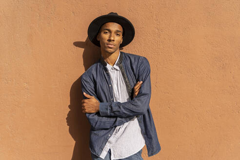 Portrait of stylish young man wearing a hat at a wall - AFVF04685