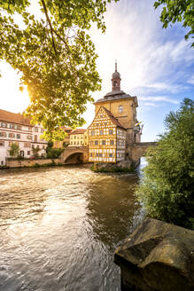 Germany, Bavaria, Bamberg, Regnitz river in front of historical town hall at sunset - PUF01744