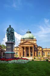 Germany, Hesse, Bad Homburg vor der Hohe, Statue of emperor Wilhelm I with Kaiser-Wilhelms-Bad in background - PUF01747