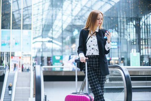 Young woman with suitcase and cell phone at train station - KIJF02860