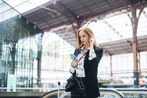 Young woman with earphones and cell phone at train station - KIJF02863