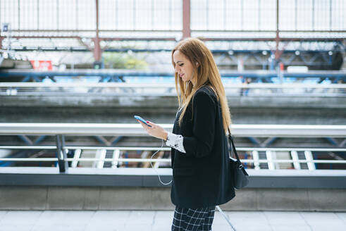 Young woman with earphones and cell phone on the go at train station - KIJF02869