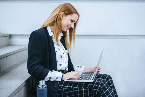 Young businesswoman sitting on stairs using laptop - KIJF02872