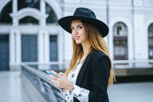 Smiling young woman with cell phone wearing a hat at train station - KIJF02887