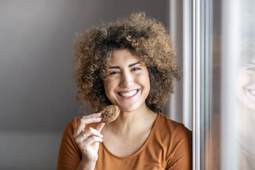 Smiling mid adult woman eating a cookie - FMKF06061