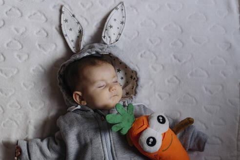 Portrait of sleeping baby girl in a rabbit hoodie lying on white blanket - GEMF03381