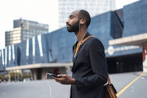 Young businessman with listening music with earphones and smartphone outdoors - JSRF00694