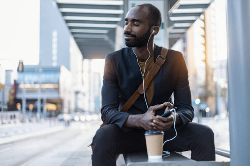 Young businessman with coffee to go listening music with earphones and smartphone relaxing at tram stop - JSRF00706