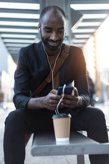 Smiling young businessman sitting at tram stop using earphones and smartphone - JSRF00709