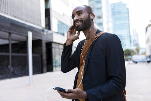 Smiling young businessman listening music with earphones and smartphone  in the city - JSRF00727