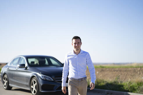 Portrait of smiling young businessman with car on country road - CJMF00222