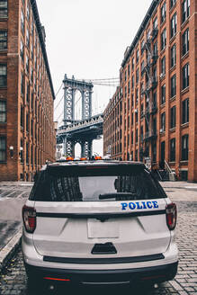 USA, New York, New York City, Police car on street with Manhattan Bridge in background - CJMF00228