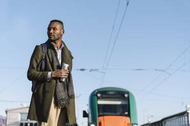 Portrait of stylish man with reusable cup waiting for the train - AHSF01630