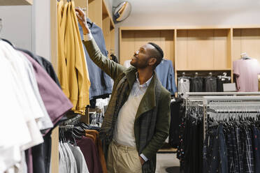 Stylish man shopping in a clothes store - AHSF01642