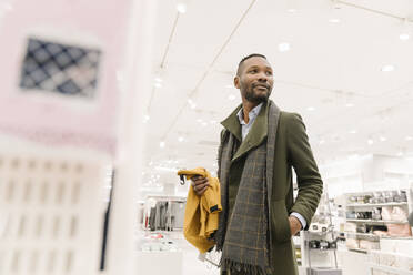 Stylish man shopping in a clothes store - AHSF01645