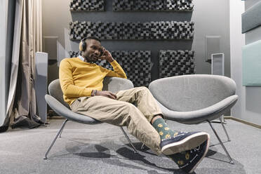 Man with headphones sitting in armchair - AHSF01648